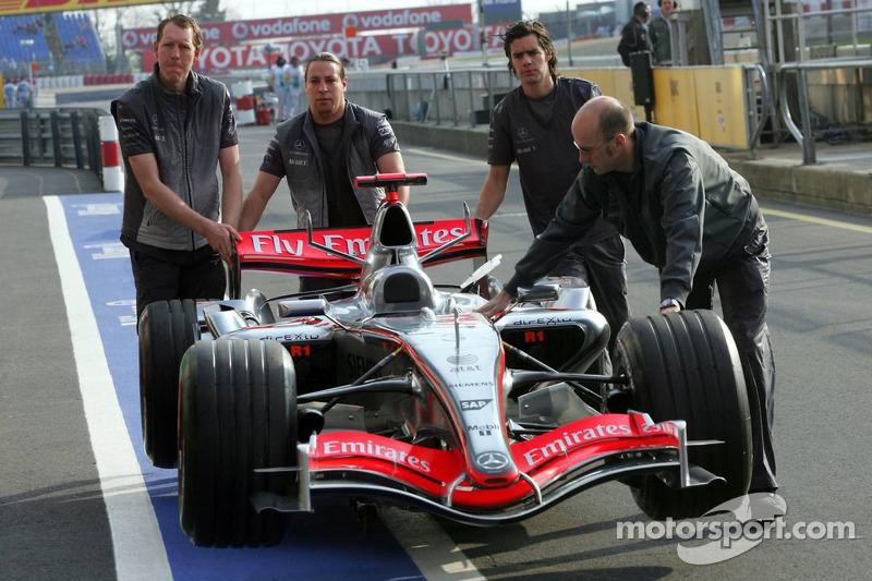 L'équipe McLaren Mercedes pousse la voiture vers les stands