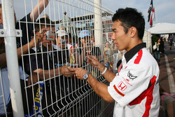 Takuma Sato signe des autographes