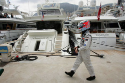 Kimi Raikkonen walks along the dock after retiring