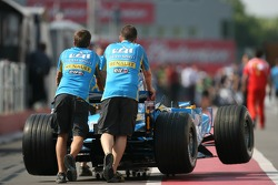Renault team members push car to technical inspection line