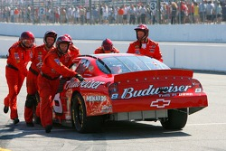 Crew members of the #8 Budweiser Chevrolet, push the car up pit road to the garage after the engine expired