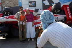 A woman wearing a scarf photographs a family in front of a GP2 Racing car in downtown Istanbul