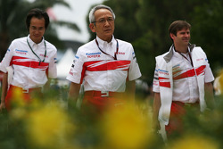 Team Principal Tsutomu Tomita arrives at Sepang flanked by engineers