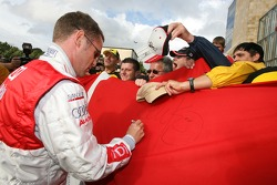 Tom Kristensen gets out of his car to sign a flag of Denmark