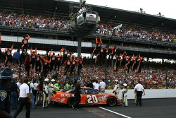 Race winner Tony Stewart and his crew climb the fence