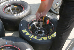 Crews roughen up the area on the tire rim to glue on the lug nuts