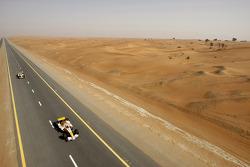 Ромен Грожан и Адам Хан за рулем машин Renault F1 R28 едут по шоссе в Дубае