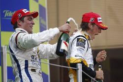 Romain Grosjean celebrates his victory on the podium with team mate Vitaly Petrov
