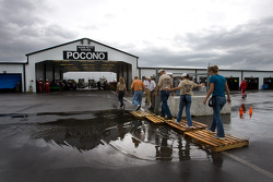 Fans try to avoid the puddles after rain delays practice