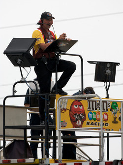 Joe Gibbs Racing Toyota crew member watches practice from atop his hauler