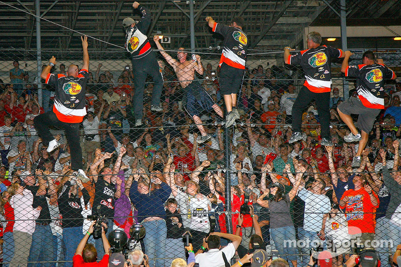 Tony Stewart, driver of the #14 Bass Pro Shops Chevrolet celebrates with his team by climbing the fence for the fans after winning