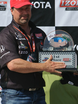 Michael Andretti accepts the team owner trophy, covering up the part that says 'Driver'